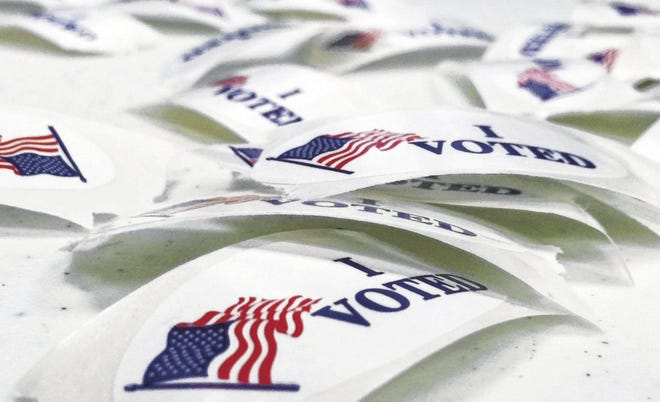 """""""I VOTED"""" stickers lie on a table."""