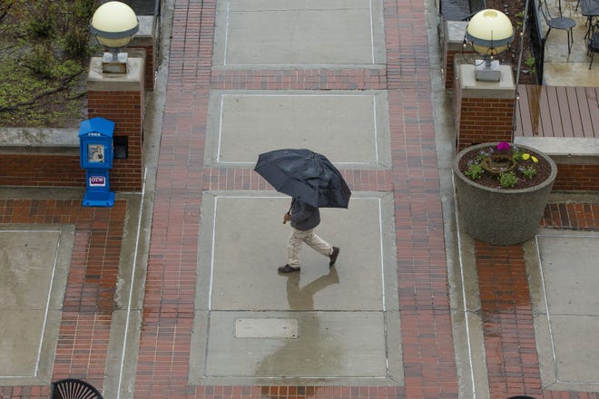 In this file photo, a pedestrian tries to keep dry under an umbrella while walking on South Michigan Street in downtown South Bend. Several more days of rain are forecast for the region.