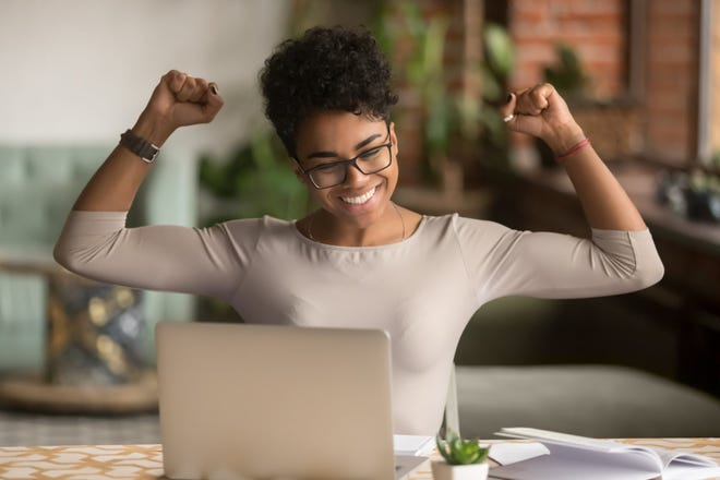 A person raising their arms in triumph in front of a computer.