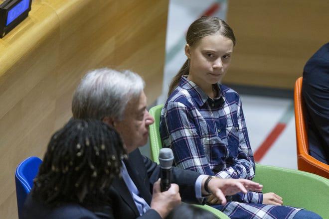 Swedish environmental activist Greta Thunberg, right, listens to U.N. Secretary-General Antonio Guterres, left, during the Youth Climate Summit at United Nations headquarters, Saturday.