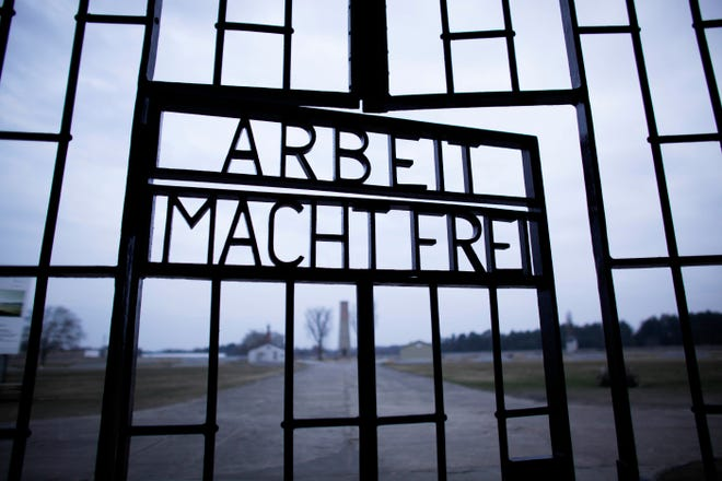 FILE - This Jan. 27, 2012, file photo shows the words 'Arbeit Macht Frei' (Work Sets You Free) at the main entrance of the Sachsenhausen Nazi concentration camp on the international Holocaust remembrance day in Oranienburg, Germany. (AP Photo/Markus Schreiber, File)