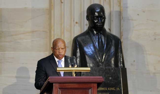 Rep. John Lewis, D-Ga, stands in front of a statue of the Rev. Martin Luther King Jr. as he speaks during a 50th anniversary ceremony for the Civil Rights Act of 1964 last week on Capitol Hill. (AP Photo)