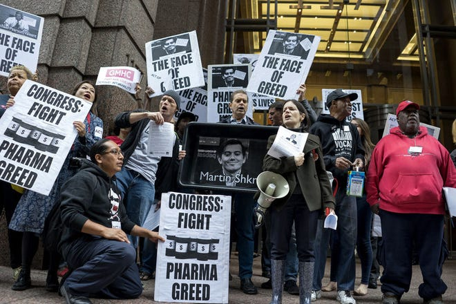 Activists hold signs containing the image of Turing Pharmaceuticals CEO Martin Shkreli, in front the building that houses Turing's offices in New York, in Juen during a protest highlighting pharmaceutical drug pricing.
