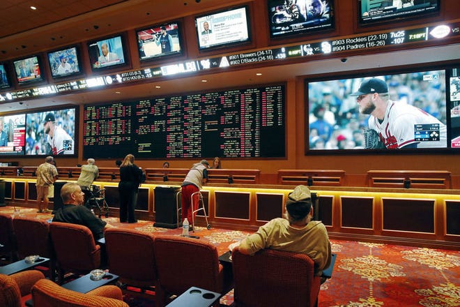 People make bets in the sports book at the South Point hotel and casino last week in Las Vegas. Now that the U.S. Supreme Court has cleared the way for states to legalize sports betting, the race is on to see who will referee the multi-billion-dollar business expected to emerge from the decision. John Locher   Associated Press