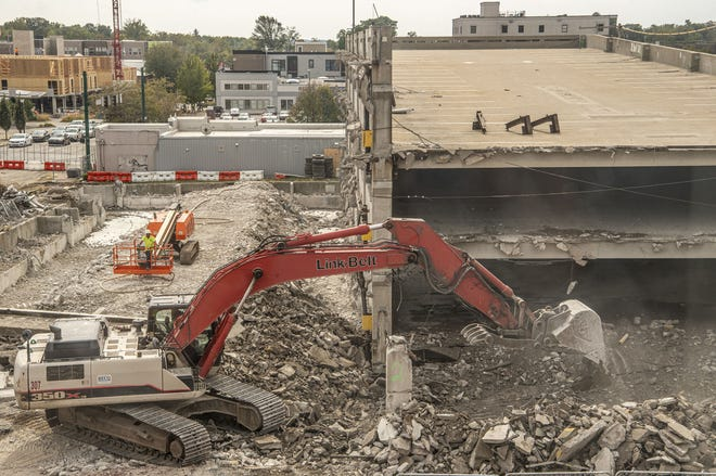 Construction crews work to take down the Fourth Street parking garage in downtown Bloomington. It has been replaced by a new, larger structure that will open Monday. (Rich Janzaruk / Herald-Times)