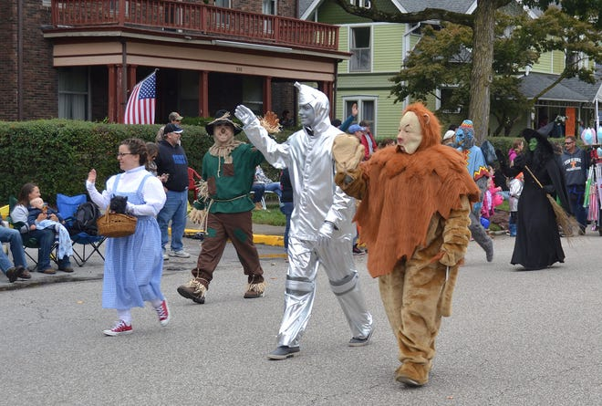 The Wizard of Oz characters — better known as employees of Home Bank — smile and wave to the crowd during the 2018 Fall Foliage Festival Parade.