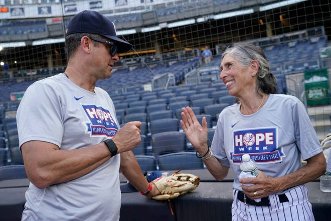Gwen Goldman, 70, right, speaks with New York Yankees manager Aaron Boone on the field before assuming her duties as a bat girl during a baseball game between the Yankees and the Los Angeles Angels, Monday, June 28, 2021, at Yankee Stadium in New York. Goldman wrote to Yankees general manager as a 10-year-old asking to be a bat girl, but was told she had no place in the dugout. Thanks to current Yankees manager Brian Cashman, Goldman got her wish on the first day of HOPE week Monday. (AP Photo/Kathy Willens)