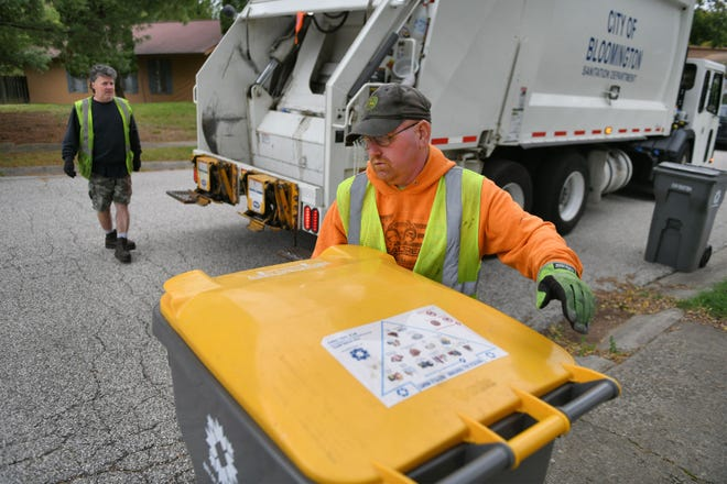 Bloomington sanitation crew members Sheldon Kinser, foreground, and Mike Courter load recycling into the back of a truck as Eric Richardson drives through the Green Briar neighborhood in 2018.