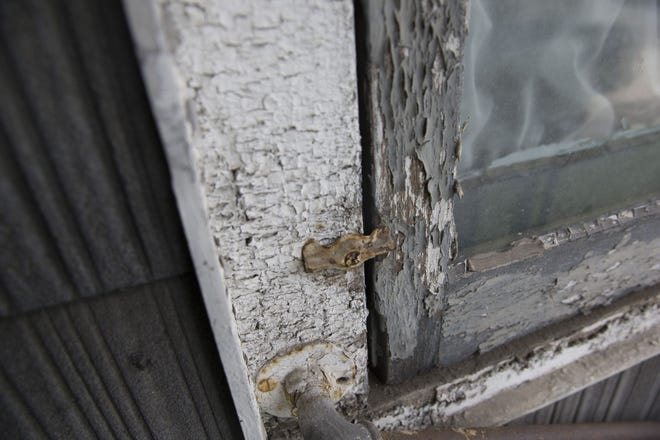 Chipped lead paint surrounds a window. Four cities in Rhode Island accounted for 69% of the recorded elevated lead levels found in children.