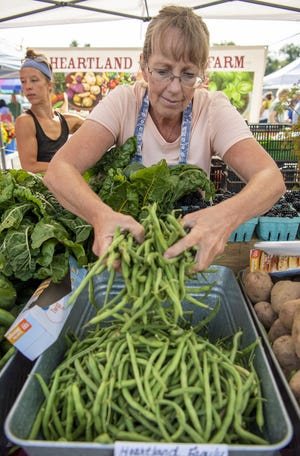 Teresa Birtles stocks the beans at a farmers' market in the old Kmart parking lot on East Third Street. (Rich Janzaruk / Herald-Times)