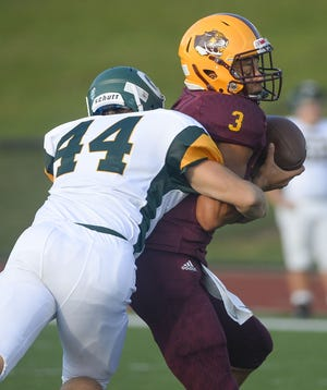 Bloomington North's Reece Lozano is sacked during the game against Greenwood at Bloomington North in Bloomington, Ind., on Friday, August 23, 2019.