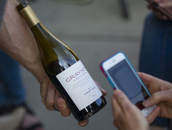 In this 2019 Tribune file photo, a Wine Walk participant takes a photo of wine bottles at Hammer and Quill in downtown South Bend.
