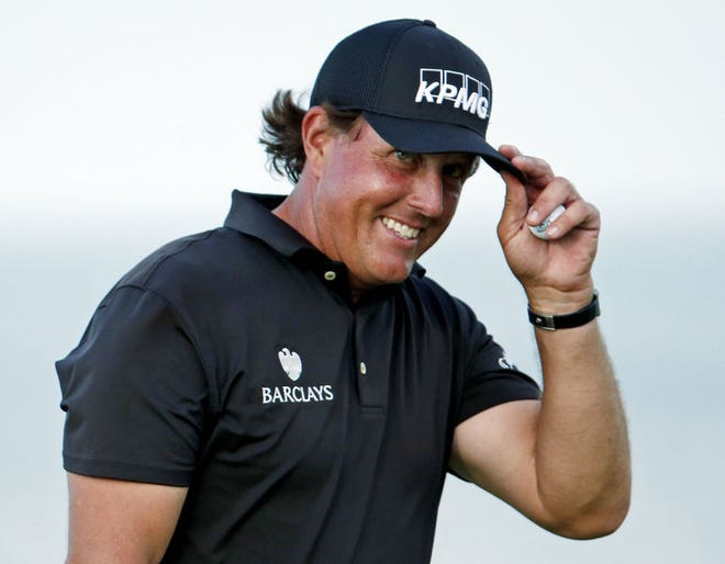 Phil Mickelson smiles after making a birdie putt on the 16th hole during the first round of the PGA Championship golf tournament Thursday, Aug. 13, 2015, at Whistling Straits in Haven, Wis. (AP Photo/Julio Cortez)