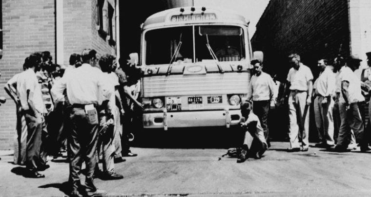 In this photo from May 15, 1961, an unidentified white man sits in front of a Greyhound bus to prevent it from leaving the station with a load of Freedom Riders testing bus station segregation in the South in Anniston, Ala. The bus was stopped by a flat tire and surrounded by a white crowd outside Anniston, and burned a short time later.