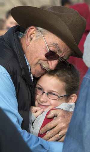 Dave Adams, an Army veteran, gives a hug to Charleigh Sullivan, his granddaughter, during a Veterans Day ceremony .