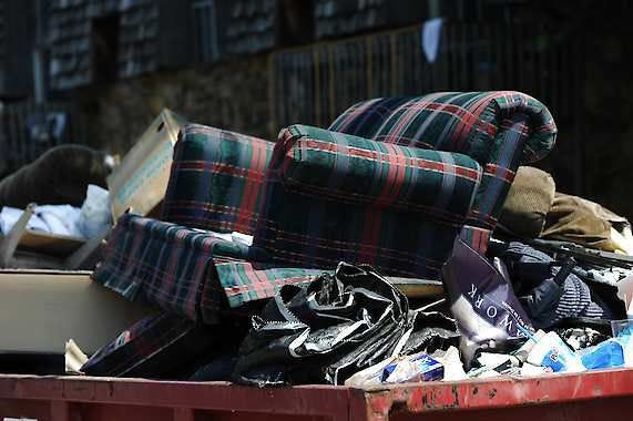 Furniture and trash overflow out of temporary dumpsters. Instead of sending things to the landfill, those looking to declutter have several options to choose from in sending still-usable items to people who can use them.