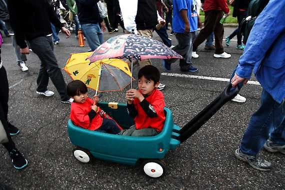 Jaden Chachich, 2, of Wixom weathers the rain with his brother Lukas, 5, as their dad Mike pulls them during the 37th annual Focus Hope walk in Detroit, Sunday, Oct. 14, 2012. (AP Photo/Detroit Free Press, Mandi Wright)