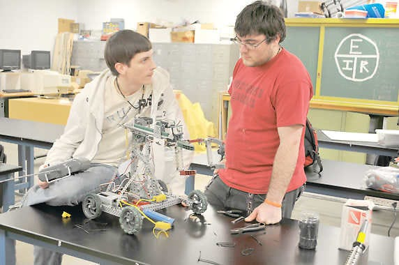 Martinsville High School seniors Danny Blackwell and Neal Fashimpaur work on one of two robots they used to compete in a robotics tournament at Zionville High School. File photo.