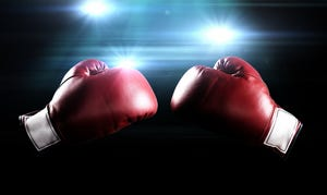 Two red boxing gloves facing each other with lights shining in the background.