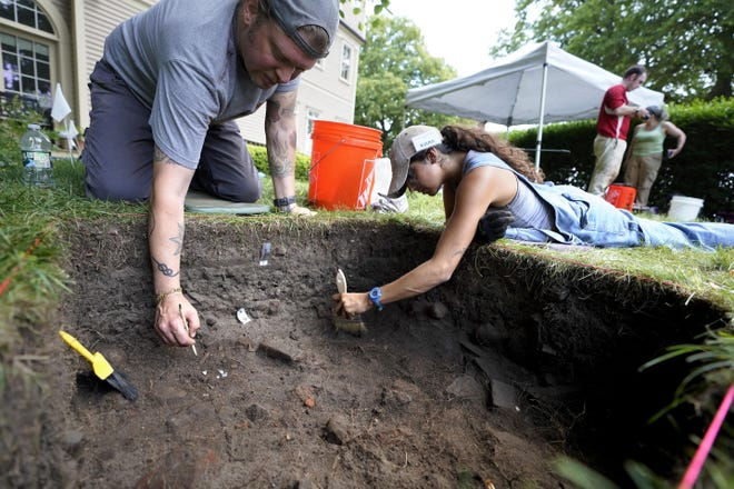 University of Massachusetts Boston graduate students Nicholas Densley, of Missoula, Mont., left, and Kiara Montes, of Boston, right, use brushes while searching for artifacts at an excavation site June 9 on Cole's Hill in Plymouth, Mass.
