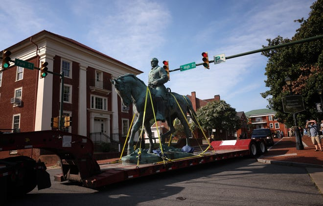 A flatbed truck carries a statue of Confederate Gen. Robert E. Lee in Charlottesville, Va., on Saturday.