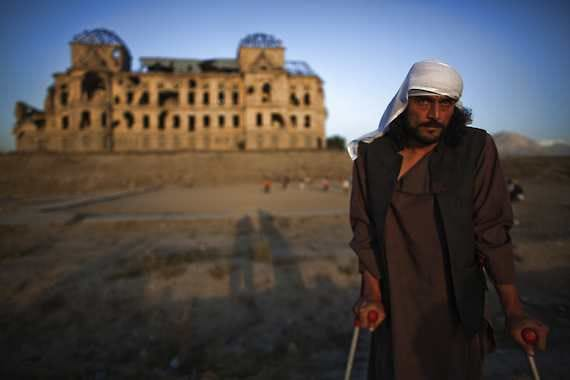 Wahidullah, 32, whose spine was pierced by a bullet during the civil war that left him crippled, poses for a photograph Thursday in front of Darul Aman Palace, which was damaged during the civil war in Kabul, Afghanistan. Wahidullah was a teenager when he fought in west Kabul during the civil war.Dusan Vranic   Associated Press