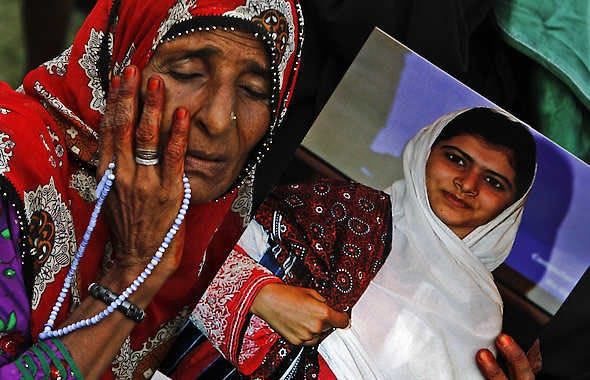 A supporter of Pakistani political party Muttahida Qaumi Movement reacts while holding a poster of 14-year-old Malala Yousufzai during a rally in Karachi, Pakistan, Sunday.Shakil Adil   Associated Press