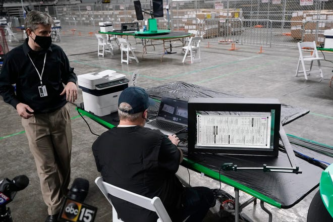 Doug Logan, left, owner of Cyber Ninjas, a Florida-based consultancy, talks about overseeing a 2020 election ballot audit ordered by the Republican-led Arizona Senate at the Arizona Veterans Memorial Coliseum on April 22 during a news conference in Phoenix.