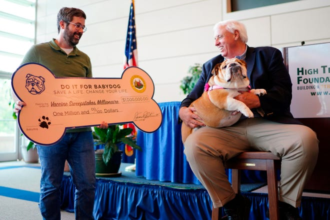 """Timothy Jackson, the latest million-dollar winner in West Virginia's vaccination sweepstakes, poses with Gov. Jim Justice and his pet English bulldog, Babydog, on Wednesday at West Virginia University's Robotic Technology Center in Fairmont, W.Va. Justice's pup is the mascot of the """"Do It for Babydog"""" vaccination giveaway."""