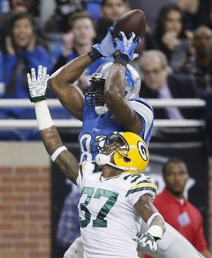 Detroit Lions wide receiver Calvin Johnson, defended by Green Bay Packers cornerback Sam Shields (37), holds on to the ball in the end zone for a touchdown during the first half of an NFL football game, Thursday, Dec. 3, 2015, in Detroit. (AP Photo/Duane Burleson)