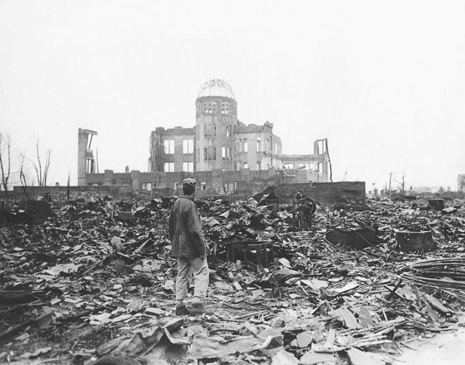 FILE - In this 1945 file photo, an Allied war correspondent stands in the ruins of Hiroshima, Japan, just weeks after the city was leveled by an atomic bomb.