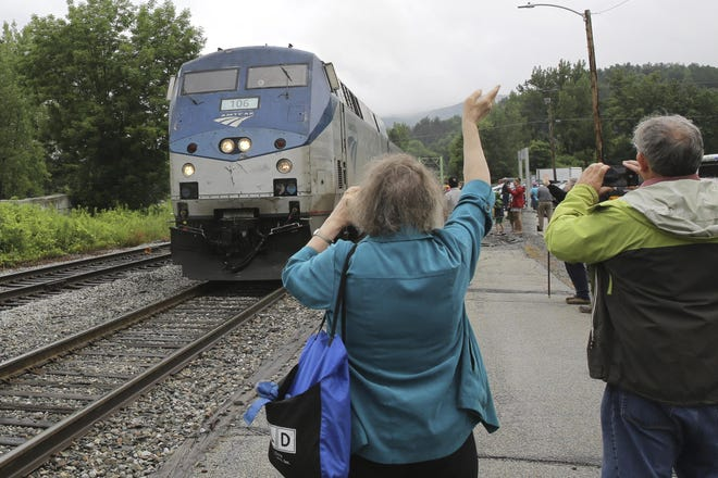 An onlooker waves as the Amtrak Vermonter passenger train arrives at the Montpelier station in Berlin, Vt., on Monday. A celebration was held at Amtrak stations across Vermont to mark the return of the passenger trains to Vermont for the first time since they were suspended at the beginning of the COVID-19 pandemic.