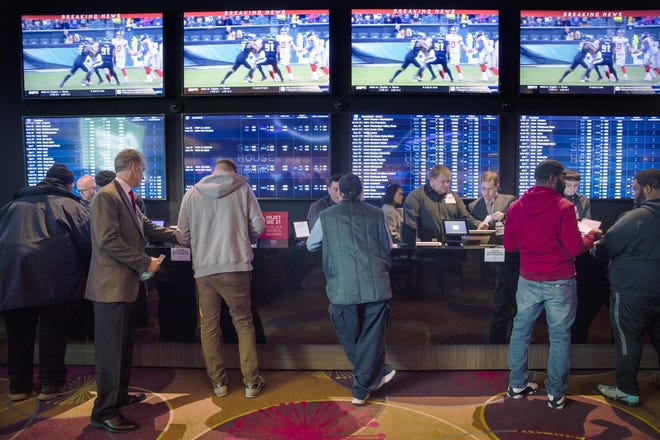 Gamblers place bets at the temporary sports betting area at the SugarHouse Casino in Philadelphia. State regulators say Pennsylvania smashed its record for gambling revenue, reporting nearly $3.9 billion in the last fiscal year as every category of wagering showed growth in one of the nation's largest casino and gambling states.