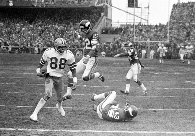 """Cowboys receiver Drew Pearson nears the end zone on a game-winning 50-yard TD pass play late in the fourth quarter of an NFC playoff game against the Vikings in Bloomington, Minn., Dec. 28, 1975. Cowboys QB Roger Staubach explained his game-winning throw by saying, """"I closed my eyes and said a Hail Mary."""" (AP Photo/File)"""