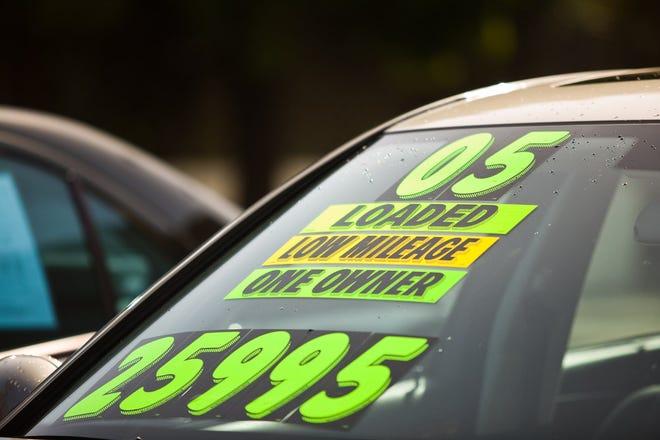 معلومات الإعلان على الزجاج الأمامي للسيارة المستعملة في الوكالة.