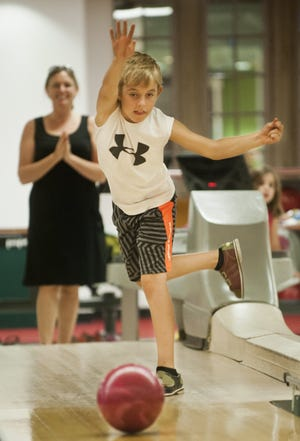 Izaak Green, along with his mother, Tara, and younger sister, Addison, knocked down some pins to celebrate Izaak's ninth birthday, which was Monday. The celebration was at the Indiana Memorial Union bowling alley on the Indiana University campus. Matthew Hatcher