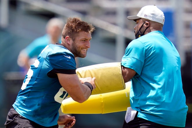 FILE - Jacksonville Jaguars tight end Tim Tebow, left, performs a drill during an NFL football team practice in Jacksonville, Fla., in this Thursday, May 27, 2021, file photo. Tebow will open training camp Wednesday, July 28 as Jacksonville's fourth- or fifth-string tight end, not all that surprising given he's closing in on his 34th birthday, started playing the position five months ago and is trying to return to the NFL after spending the previous five years in the New York Mets' organization. (AP Photo/John Raoux, File)