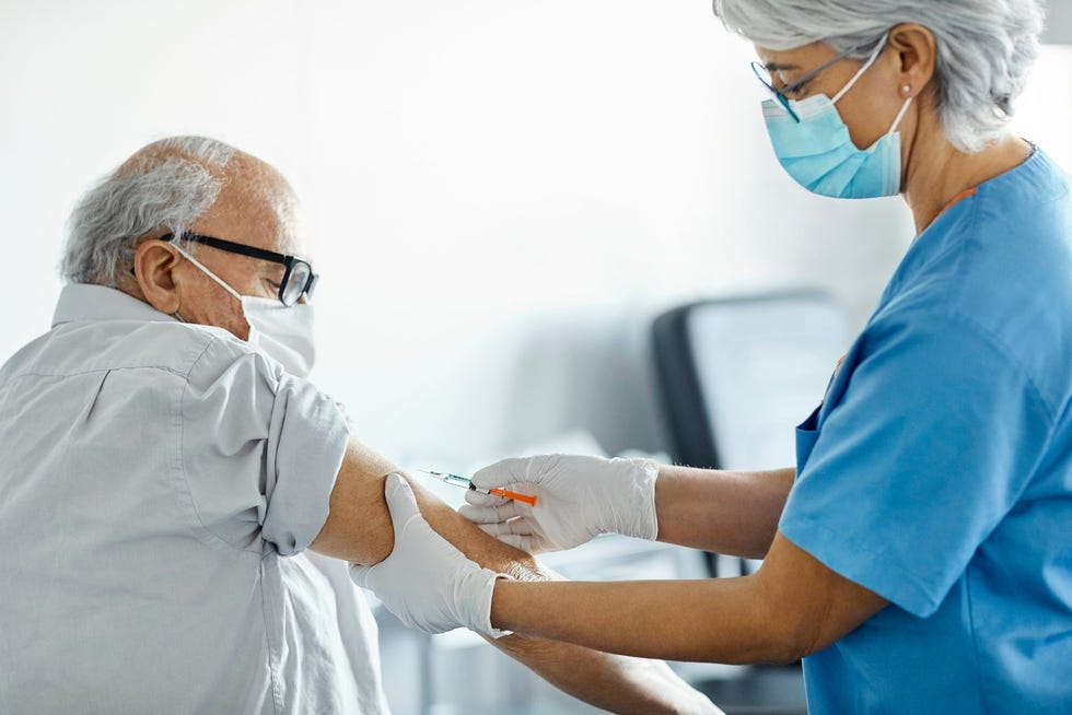 A nurse vaccinates an older person in a clinic.