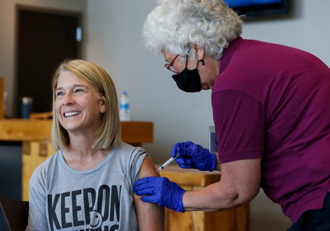 Karen Martin receives a COVID-19 vaccine shot from retired RN Barbara Vicente at a vaccination clinic hosted by James River Church West Campus in conjunction with Jordan Valley Community Health Center in Springfield, Mo., on July 12, 2021.
