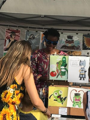 Shoppers look at artwork at one of the more than 70 booths at the Brighton Wine, Art and Music Festival on Friday, July 30.