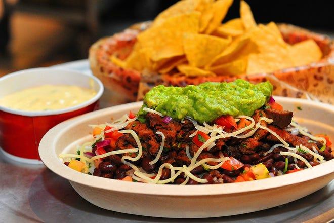 Un tazón de burrito de chipotle está en el primer plano de la foto, que incluye nachos y salsa para mojar.