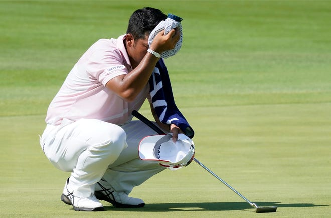 Hideki Matsuyama of Japan dries his sweat on the 12th green during the third round of the men's golf event at the 2020 Summer Olympics Saturday, July 31, 2021, in Kawagoe, Japan.