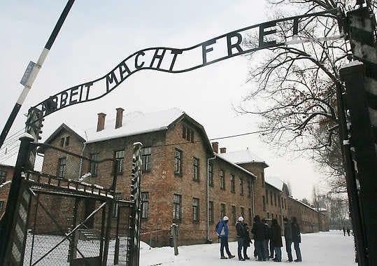"""Tourists pause near the main entrance to the former Nazi death camp Auschwitz Birkenau, Friday in Oswiecim, southern Poland, where a replica of the inscription """"Arbeit Macht Frei,"""" (""""Work Sets You Free"""") is posted. The original infamous iron sign with its cynical slogan was stolen before dawn on Friday and the police have launched an intensive search, but the symbolic inscription above the entrance has been replaced by a replica sign. Associated Press"""