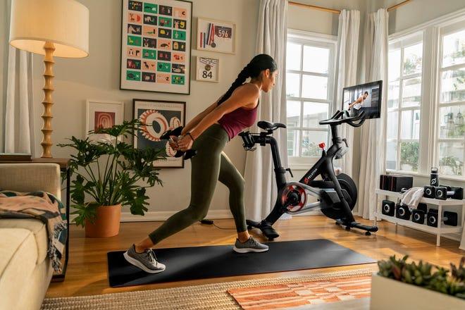 Person exercises on mat next to a Peloton Bike