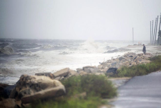 A man, back right, stands on the edge of Alligator Drive in Alligator Point, Fla., as Tropical Storm Fred brings strong winds and rain to Florida's Forgotten Coast, Monday, Aug. 16, 2021. (Tori Lynn Schneider/Tallahassee Democrat via AP)