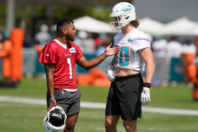 Miami Dolphins quarterback Tua Tagovailoa (1) talks to tight end Adam Shaheen (80) during an NFL football practice Saturday, July 31, 2021, in Miami Gardens, Fla. (AP Photo/Marta Lavandier)