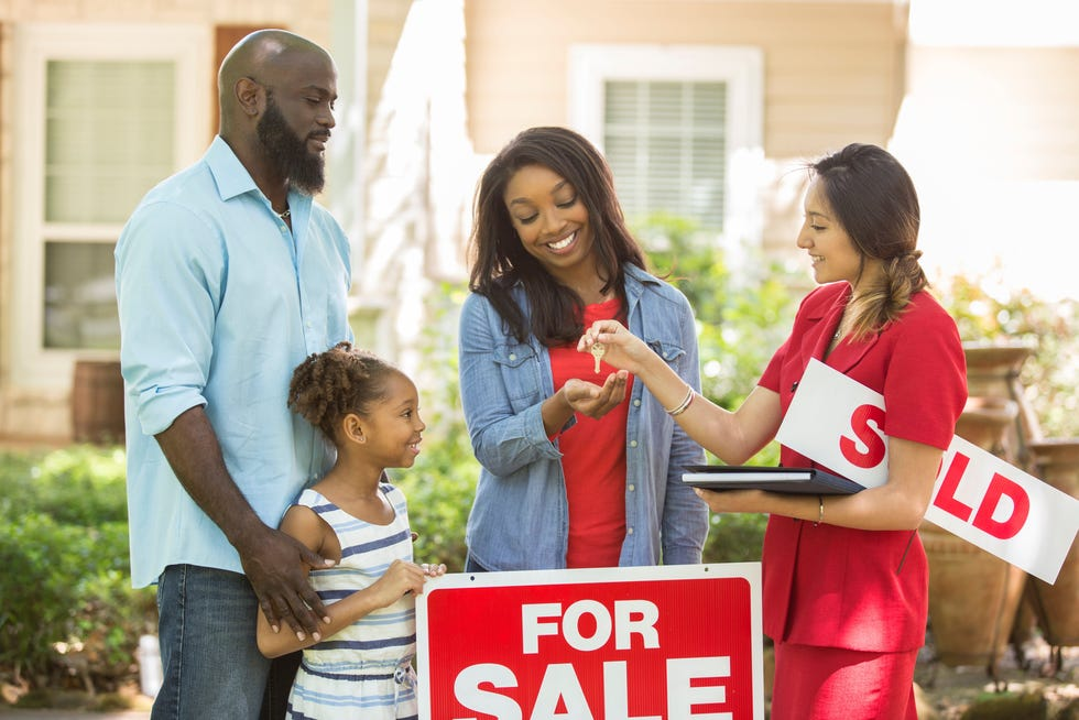 A real estate agent handing keys over to a young family in front of a sold sign and their new house