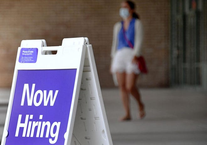 """Pedestrians walk by a """"Now Hiring"""" sign outside a store on August 16, 2021 in Arlington, Virginia. (Olivier Douliery/AFP via Getty Images/TNS)"""
