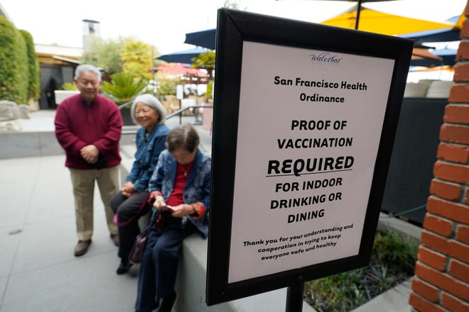 Customers wait to show proof of vaccination before entering the Waterbar restaurant on Friday, Aug. 20, 2021, in San Francisco. San Francisco became the first major city in the nation to require proof of full vaccination against COVID-19 on Friday for people dining inside restaurants, working out in gyms or attending indoor concerts. (AP Photo/Eric Risberg)