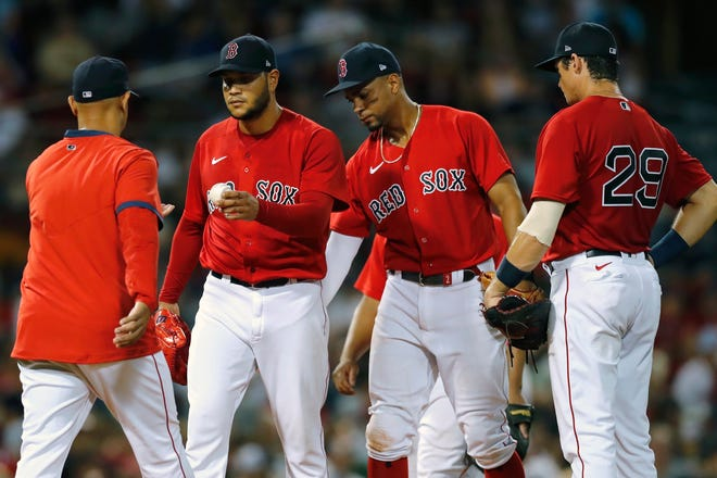 Boston Red Sox manager Alex Cora, left, relieves Eduardo Rodriguez, center left, as Xander Bogaerts, center right, and Bobby Dalbec (29) look on during the fourth inning of a baseball game against the Texas Rangers, Saturday, Aug. 21, 2021, in Boston. (AP Photo/Michael Dwyer)